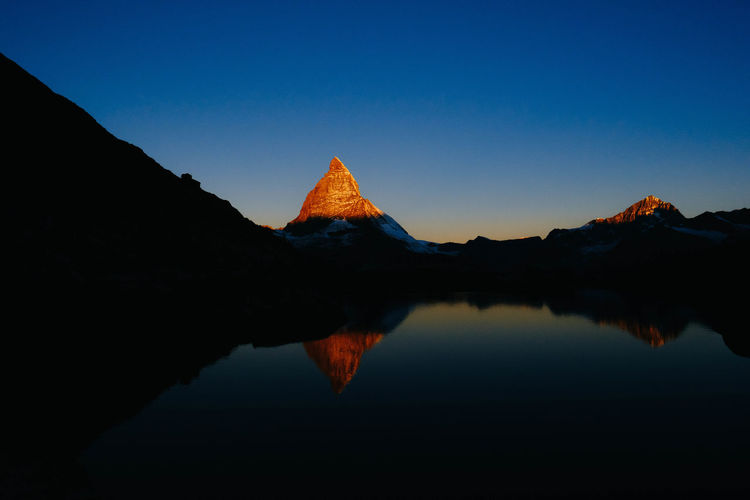 Reflection of silhouette mountain in lake against sky during sunset