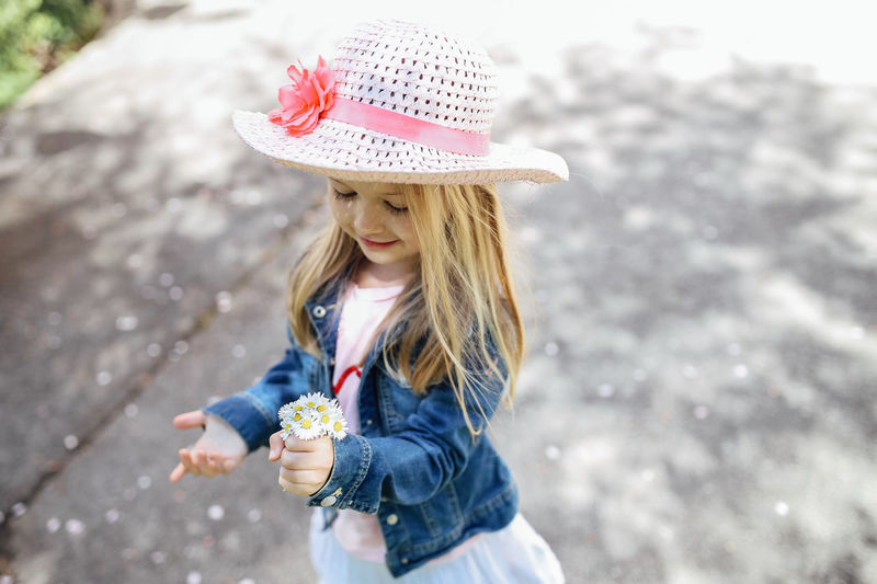 Hat Leisure Activity One Person Real People Clothing Girls Childhood Child Day Casual Clothing Holding Lifestyles Females Focus On Foreground Front View Innocence Outdoors Hairstyle Smiling Spring Springtime Sun Hat Shadow Daisy Happiness