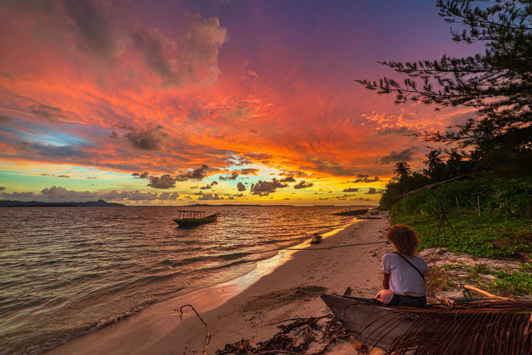 Woman sitting on beach against sky during sunset