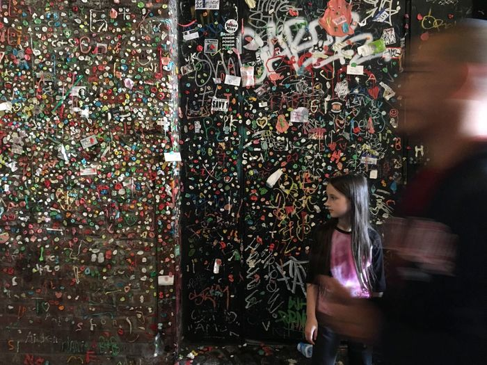 Blurred motion of man by teenage girl standing against gum wall