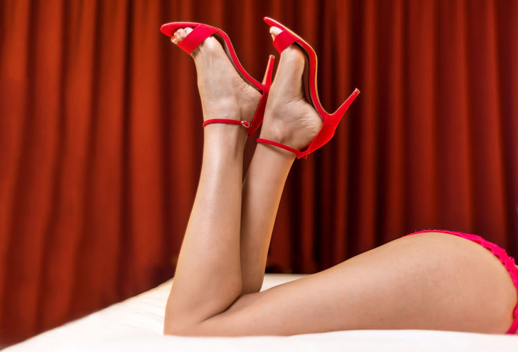 Low section of sensuous woman lying on bed