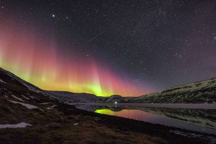 Aurora borealis on lake and landscape at night