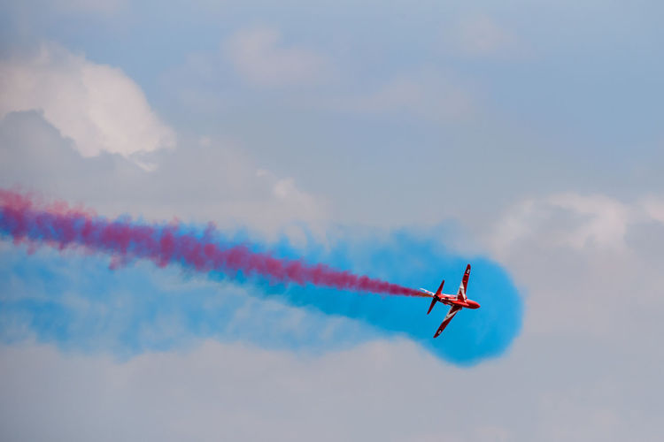 A single Red Arrow BAE systems Hawk T1 of the Royal Air Force during an air display at RIAT Fairford 2018, UK. Air Tattoo Airshow BAE Systems Hawk T1 Fairford Flying Hawk T1 RIAT Red Arrows Royal International Air Tattoo Aerobatics Air Display  Aircraft Airplanes Aviation Blue Smoke Display Team Flight International Open Air Red Smoke Royal Air Force Single Turning Weekend Airplane Air Vehicle Cloud - Sky Vapor Trail Mode Of Transportation Transportation Plane on the move Sky Fighter Plane Smoke - Physical Structure Military Airplane Motion Low Angle View Blue Multi Colored Nature No People Teamwork Formation Flying Outdoors Order
