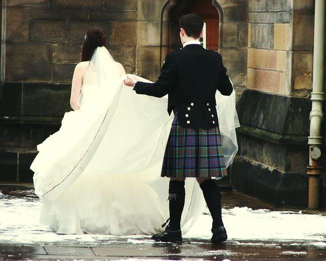 Rear View Of Bridegroom Holding Groom Wedding Dress During Winter