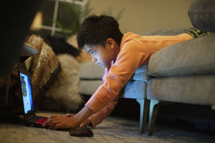 Rear view of boy looking at camera while sitting at home