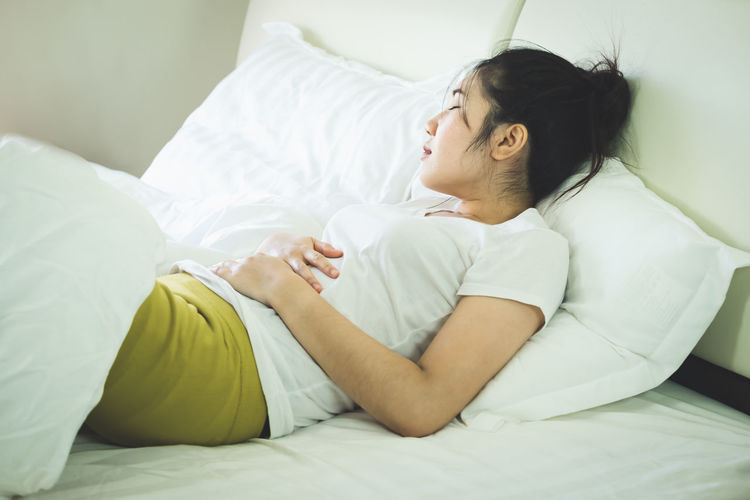 Woman with stomachache lying on bed