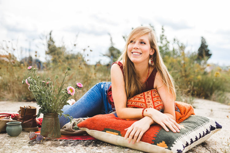 Portrait of a smiling young woman laying outdoors