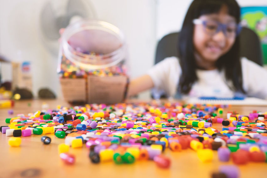 Multi Colored Indoors  Leisure Activity Child Happiness Women Casual Clothing Childhood Large Group Of Objects One Person Front View Fun Females Smiling Selective Focus Portrait Headshot Asian  Toy Blocks Beads Skill  Learning Home Happy