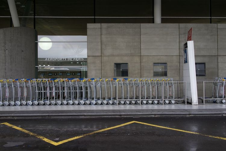 France, Paris: at Charles de Gaulle CDG airport, carts Airport Repetition Multiple Objects Horizontal Day Cart Lined Up Object Nobody No One Wet Rainy Still Life Sidewalk Transportation Architecture Built Structure No People Road Building Exterior Sign Symbol Outdoors Empty Marking Road Marking City Street Building In A Row Parking Lot Illuminated Barrier Architectural Column Concrete