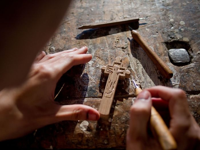 Close-Up Of Man Hand Carving Wooden Cross At Table