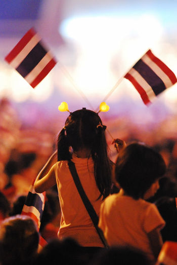 Rear view of girl holding thai flags during festival at night