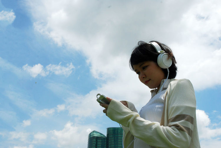Low angle view of woman listening music while using smart phone against sky