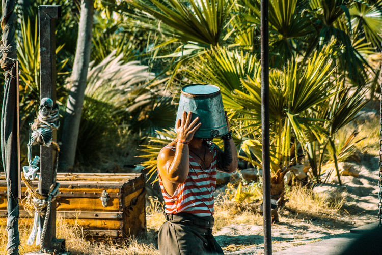Mid adult man with bucket on head standing against palm trees