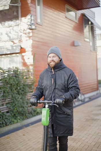 Man with bicycle on street against building in city