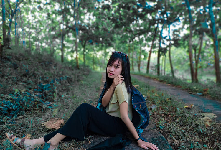 Portrait of beautiful young woman sitting on land in forest