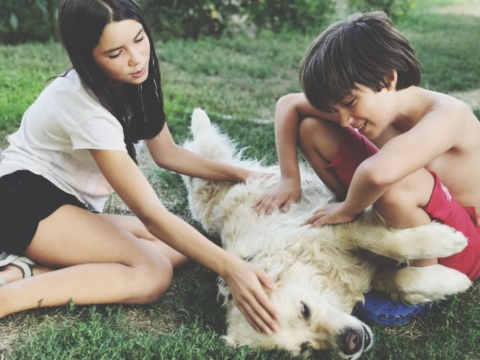 EyeEm Selects Pets Dog Grass Togetherness Childhood Domestic Animals Friendship Real People Child Boys Girls Casual Clothing Day Love Playing Bonding Animal Themes Happiness Outdoors Sitting