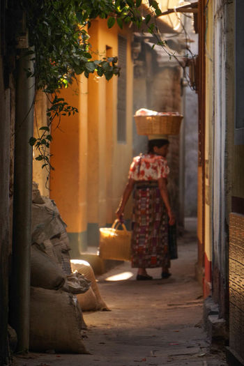 Rear View Of Woman With Wicker Basket On Head Amidst Houses