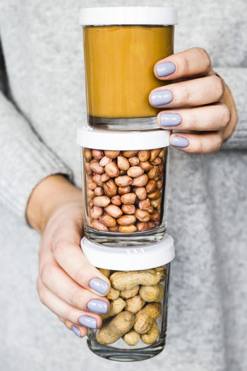 Close-up of hand holding peanut jars