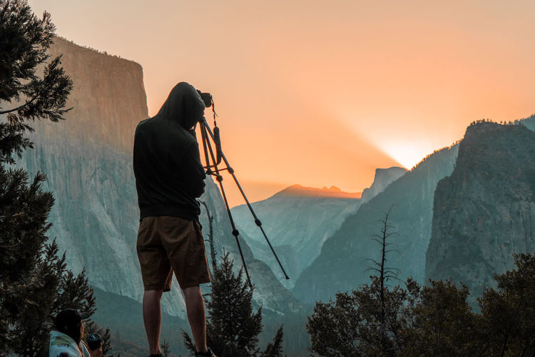 Rear view of person photographing while standing against mountain during sunset