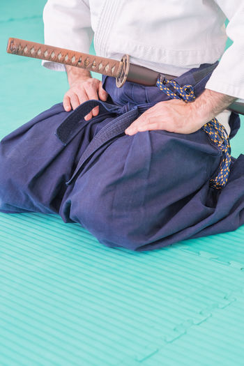 Midsection of man with samurai sword sitting on exercise mat