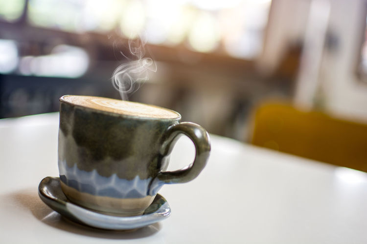The vintage color cup with steaming coffee sitting on white table with blurred cafe background, hot cappuccino Cofee Refreshment Steaming Hot Cafe Hot Drink Table Coffee Cup Freshness Latte Steam Saucer No People Tea Cup Cafeteria Beverage Warm Caffeine Aroma Foam Milk Bokeh