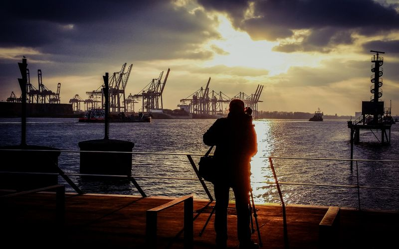 Rear view of silhouette man standing at port of hamburg during sunset