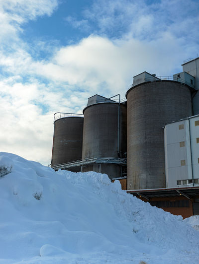 Snow covered factory against sky
