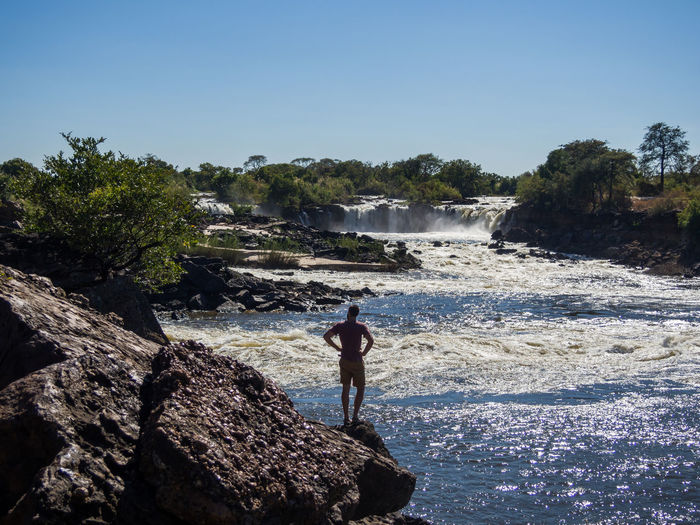 Man standing on rock at ngonye waterfall against clear sky, zambia