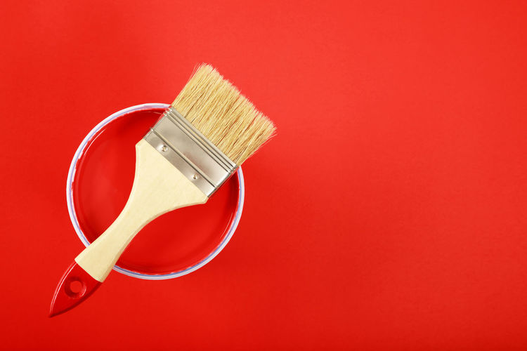High angle view of paintbrushes against red background