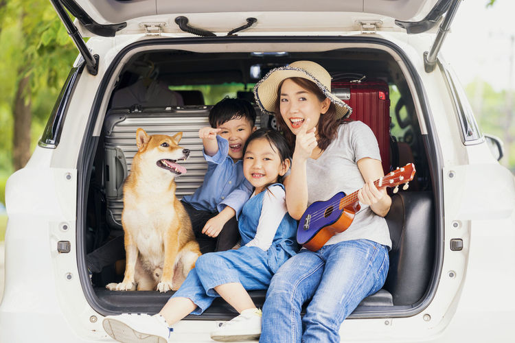 Happy family with shiba inu dog near car outdoors. a family with a mother, daughter and son