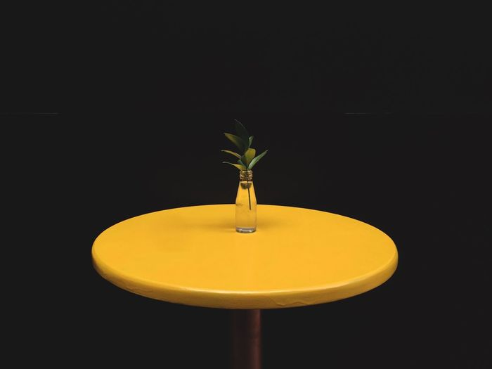 Close-Up Of Yellow Table Against Black Background