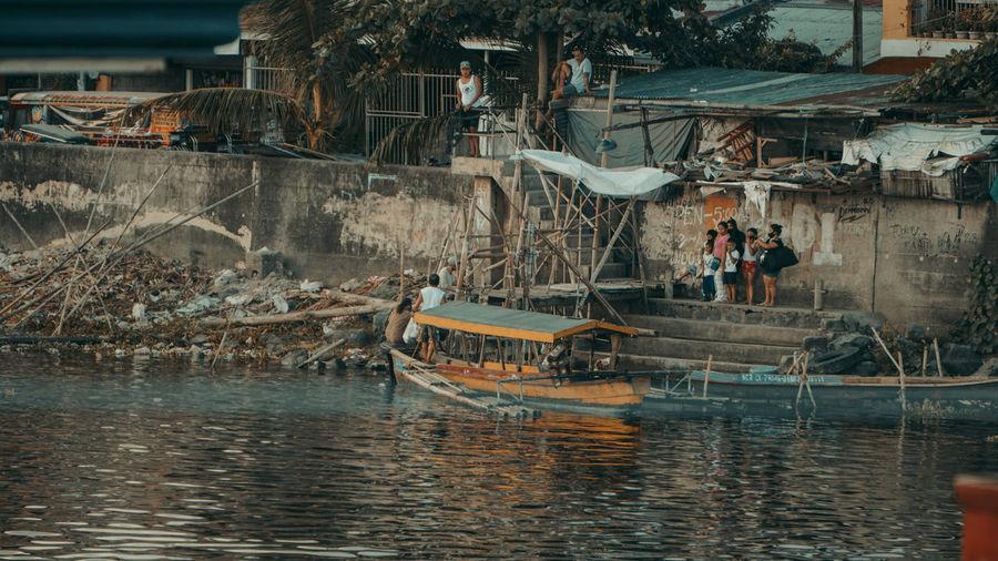 People on boat in sea against buildings