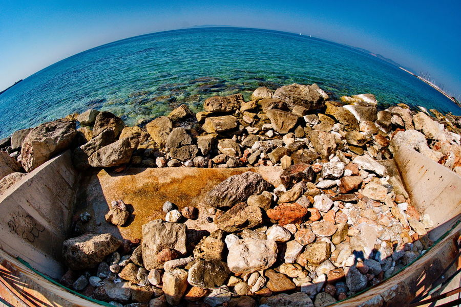 a picture ot rocks in a sea,in a beach in athens greece Athens, Greece Beautiful Beauty In Nature Blue Clear Sky Day Fish Eye Lens Horizon Over Water Nature No People Ocean Outdoors Pebble Beach Rock - Object Scenery Scenics Sea Sky Stone Stones Sunset Tranquil Scene Tranquility Water Wide Angle
