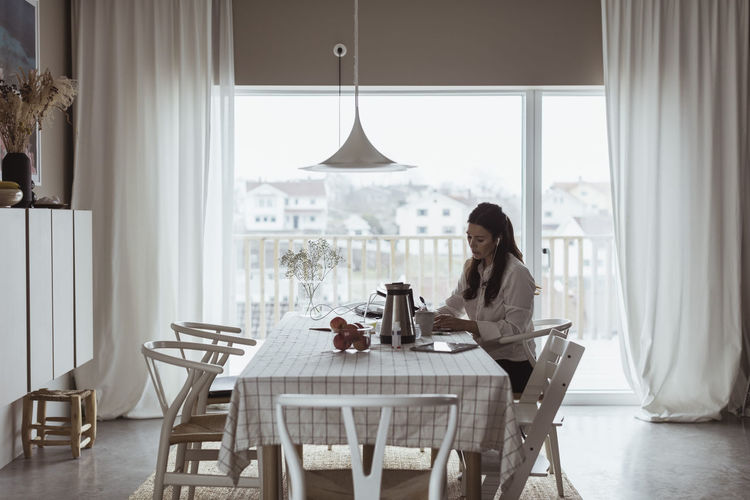 Woman sitting on table at home