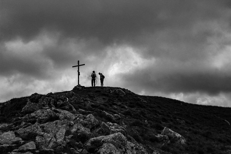 Low angle view of hikers standing by cross on mountain against storm clouds