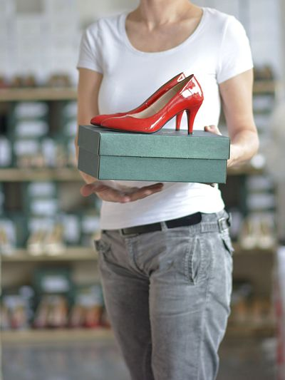 Midsection of saleswoman holding box with high heels at store