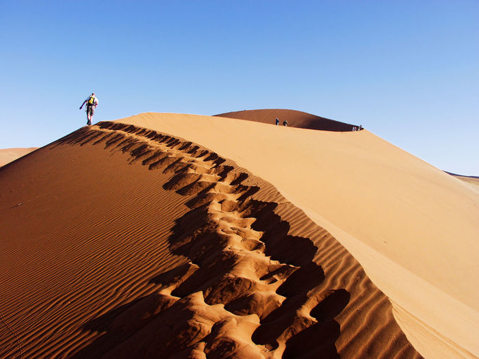 Low angle view of man on sand dune against clear sky