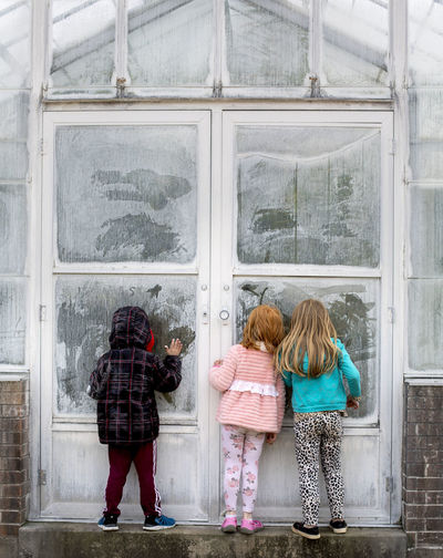 On a cloudy spring afternoon, three children peer into the doorway of a greenhouse on the campus of Southern Illinois University at Carbondale. Women Rear View Real People Full Length Window Lifestyles Day Glass - Material Architecture Built Structure Transparent Leisure Activity Casual Clothing Females Childhood People Standing Girls Child Building Exterior Outdoors Rain Warm Clothing Boy Greenhouse Green House Textured  Texture Old Building  Curious Curiosity Southern Illinois University Southern Illinois  Carbondale Carbondale, Illinois Spring Peering Peering Through Windows Door Doorway Three Children