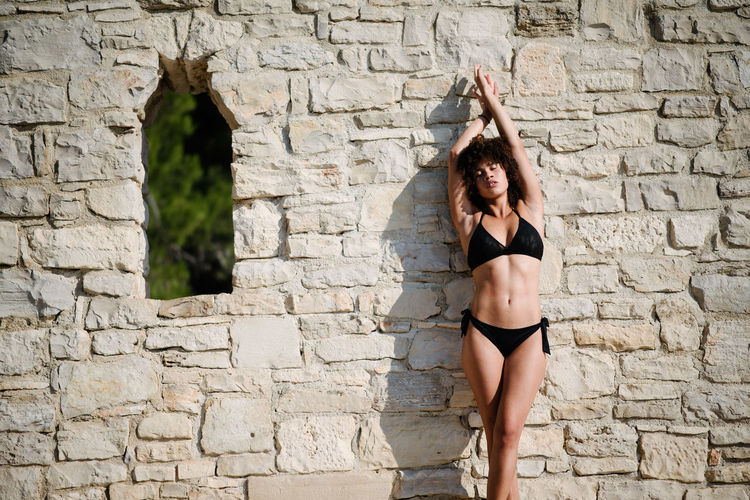 Woman standing against stone wall