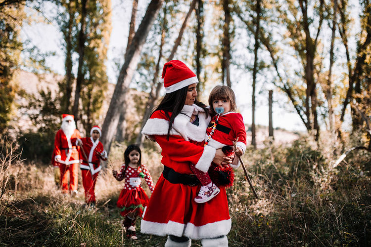 Mother carrying toddler baby while dressed as santa claus in forest