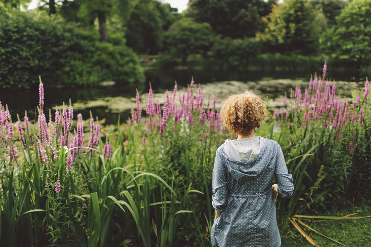Beauty In Nature Blonde Blooming Curly Hair Day Field Flower Focus On Foreground Fragility Freshness Garden Girl Grass Green Color Growth Lake Landscape Lifestyles Nature Nature Outdoors Park Plant Purple Tranquility Summer Exploratorium