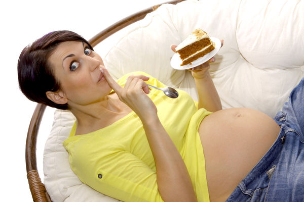 pregnant woman eats a piece of pie Hungry Woman Adult Appetite Belly Calories Casual Clothing Females Front View Gestating Gestation Gravid Healthcare And Medicine Holding Indoors  Leisure Activity Lifestyles Looking Looking Away Pregnancy Pregnant Sitting Waist Up Women Young Adult Young Women