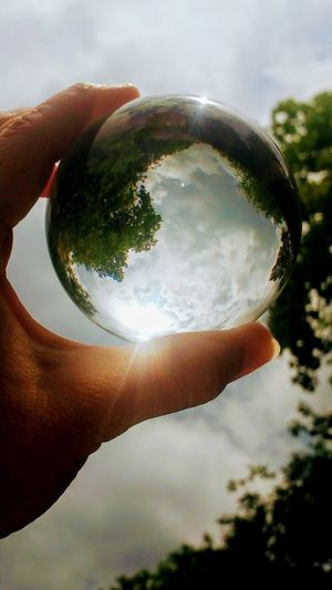 A little Crystal ball photography, while I could catch a lensflare before the dark clouds moved in. Nature Sky Outdoors Day People Close-up Human Finger Human Hand Popular Photos Naturelover Eye Em Nature Lover Beauty In Nature Sunsnap Natural Lensflare Crystal Ball Photography Sky And Clouds Trees