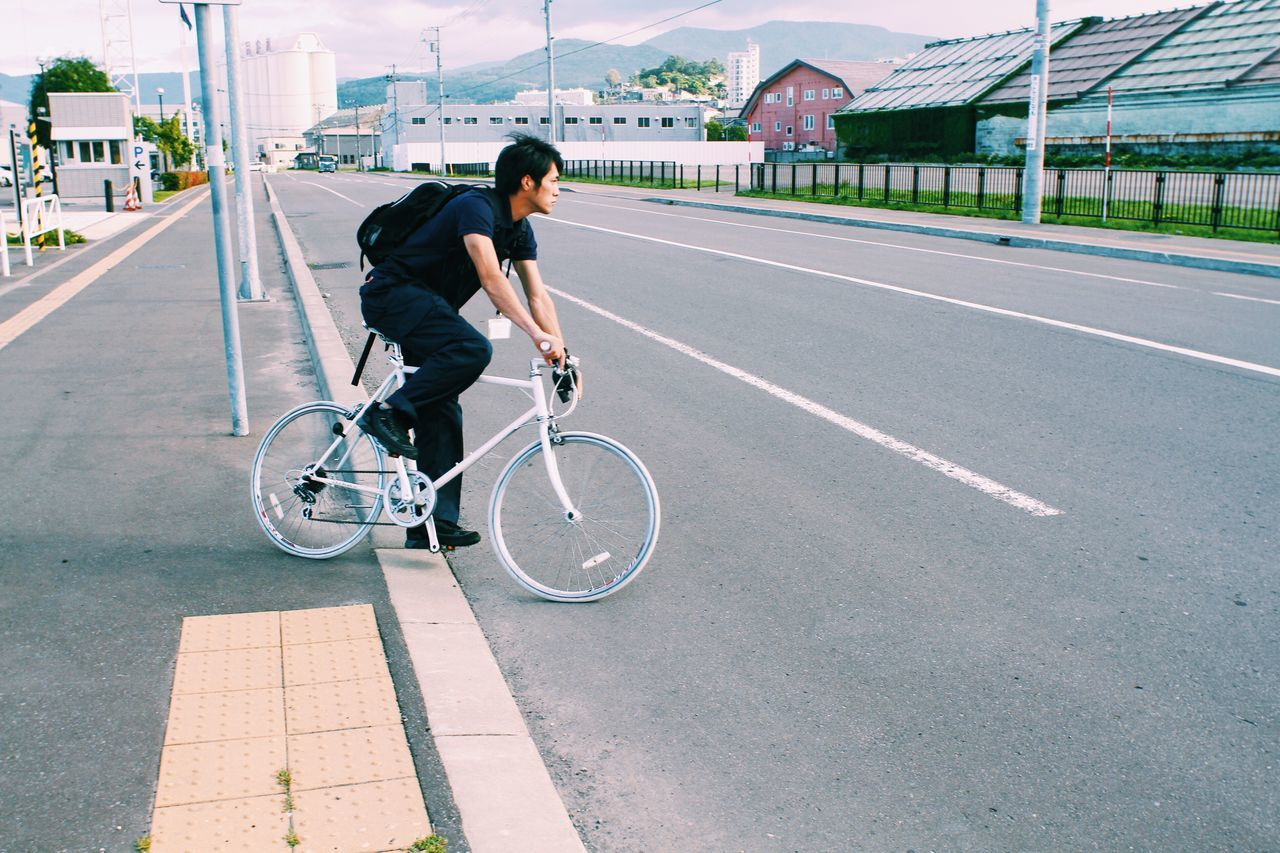 Side view of young man with bicycle on road