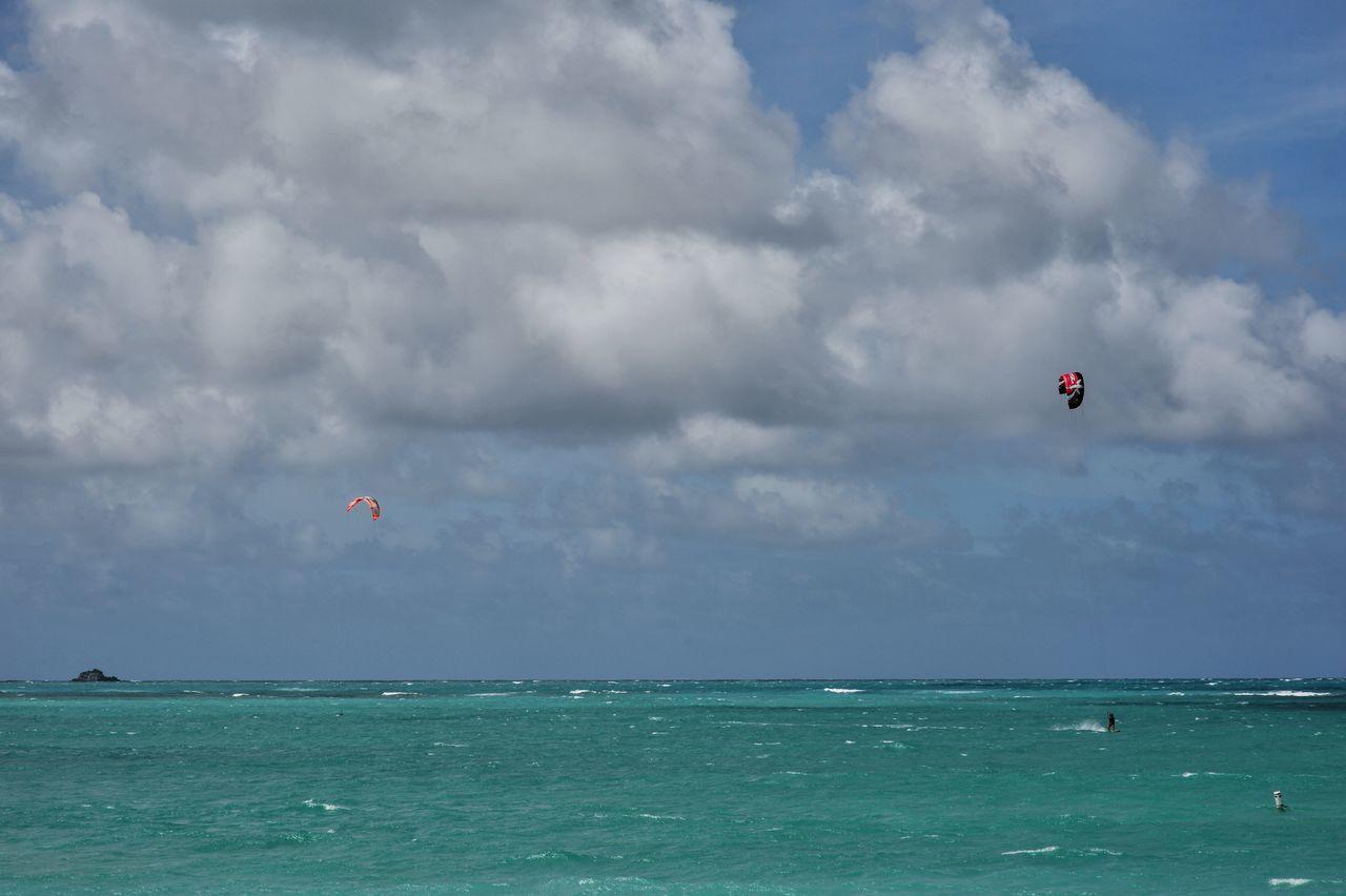 People Kiteboarding On Sea