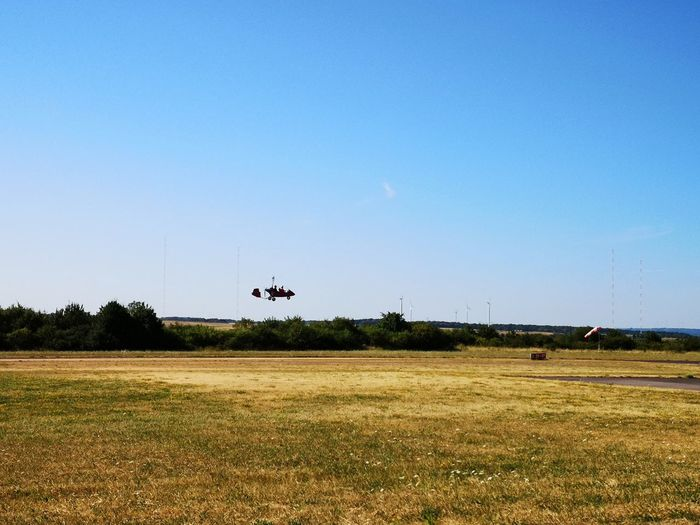 Airplane flying over field against sky
