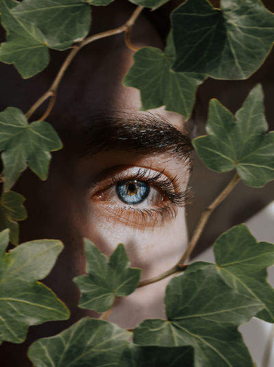 Close-up portrait of young woman with leaves