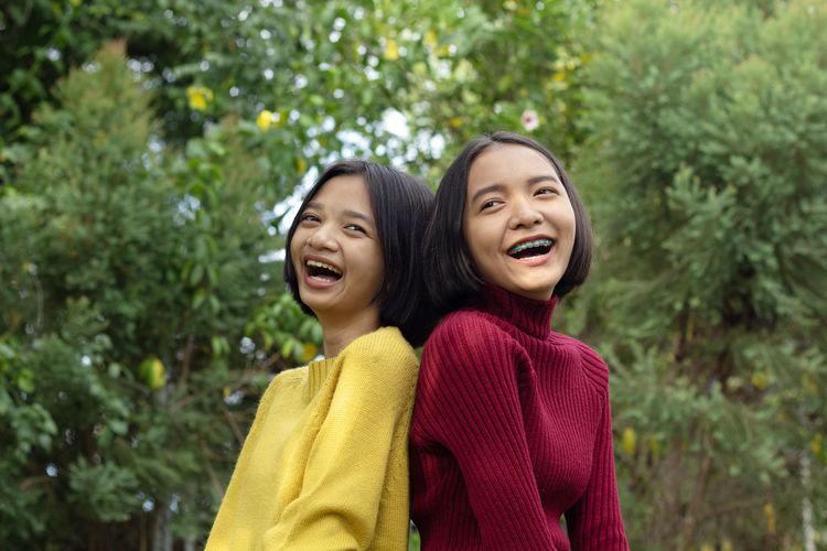 Girls standing against trees