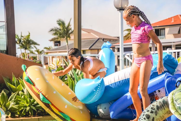 poolside fun with inflatables- young girls in swimsuits having a fun summer day by the pool Women Lifestyles Females Family Childhood Child Girls Leisure Activity Real People Pool Day Togetherness Swimming Pool Water Enjoyment Swimwear Full Length Two People Inflatable  Innocence Outdoors