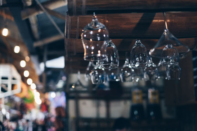 Low angle view of upside down glasses hanging from ceiling in restaurant
